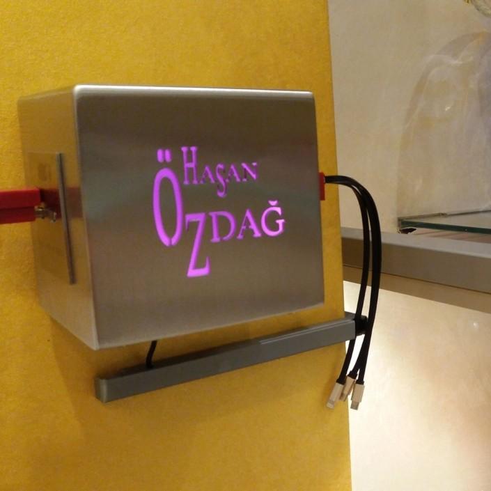 Hier sehen Sie eine Edelstahl-Ladestation/Cube der Orientalischen Feinkonditorei Hasan Özdag GmbH in Köln mit vier USB-Ladebuchsen und LED-RGB beleuchteten Logo